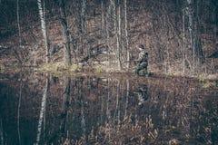 Jagdszene mit dem Jägermann, der im Sumpfgebiet mit Wald während der Jagdsaison stiehlt stockbilder
