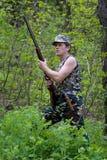 Jager in bos met kanon in handen Stock Afbeeldingen