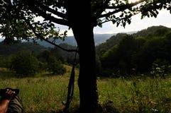 Jager die in hinderlaag door boom wachten Stock Afbeelding
