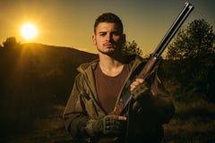 Jager die met Krachtig Geweer met Werkingsgebied Dieren bevlekken Geweer Hunter Silhouetted in Mooie Zonsondergang stock foto's