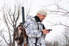 Jager die op het mobiele navigatieapparaat kijken Stock Afbeeldingen