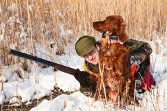 Jager en zijn jachthond die een hideout zoeken Stock Fotografie