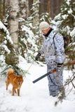 Jager met hond bij de winter de jacht royalty-vrije stock afbeelding