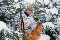 Jager met hond in de winterbos stock foto's