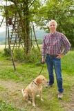 Jager met hond voor boomtribune Stock Foto