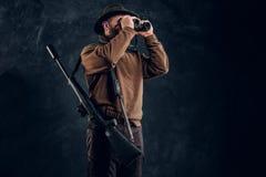 Jager met jachtgeweer het letten op door verrekijkers Studiofoto tegen donkere muurachtergrond stock afbeelding