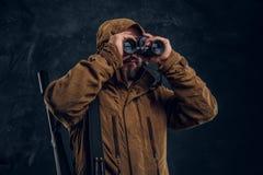 Jager met jachtgeweer het letten op door verrekijkers Studiofoto tegen donkere muurachtergrond royalty-vrije stock afbeeldingen