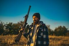 Jager met jachtgeweerkanon op jacht Gebaard de holdingskanon van de jagersmens en het lopen in bos stock afbeelding