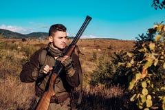 Jager met jachtgeweerkanon op jacht Hertenjacht Jager in camouflagekleren klaar om met de jachtgeweer te jagen stock fotografie