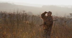 Jager met zich op het gebied bevinden en geweer die, mistige de herfstochtend, zacht zonlicht rond eruit zien stock videobeelden