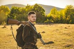 Jagersmens Jager met een rugzak en een de jachtkanon De jachtperiode, de herfstseizoen Mannetje met een kanon Een jager met a royalty-vrije stock afbeeldingen