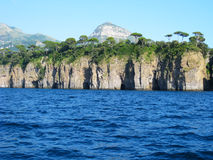 Jagged cliffs South of Sorrento Italy. View from the Mediterranean of lush forest atop the jagged cliffs South of Sorrento, Italy Stock Image