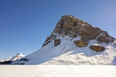 Jagged Mountain Peak Frozen Bow Lake Banff National Park Canadian Rockies Springtime. Jagged Mountain Peak towering above Frozen Bow Lake on First Day of Spring royalty free stock photo