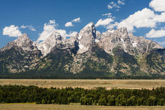 Jagged peaks of Grand Teton mountains. Jagged peaks of Teton mountains rise abruptly from the relatively flat plains of Jackson Hole into a bright blue summer Royalty Free Stock Images