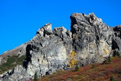 JAGGED ROCK FACE WITH VIBRANT BLUE SKY. In background and fall tundra. Taken in Alaska Royalty Free Stock Image