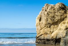 Jagged rock formation on a sandy beach at the ocean. Jagged rock formation at a sandy beach in Malibu, California on a sunny summer day Royalty Free Stock Photos