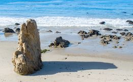 Jagged rock formation on a sandy beach at the ocean. Jagged rock formation at a sandy beach in Malibu, California on a sunny summer day Stock Image