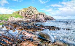 Rocky coastline on Islay, Scotland. Jagged rock layers and boulders smoothed by the ocean are seen at an intertidal zone on the island of Islay, Scotland, UK stock image