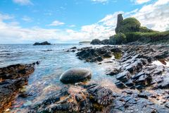Rocky coastline on Islay, Scotland. Jagged rock layers and boulders smoothed by the ocean are seen at an intertidal zone on the island of Islay, Scotland, UK royalty free stock photo