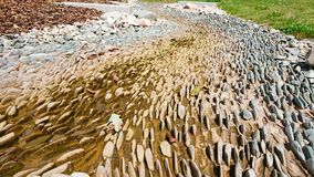 Jagged rocks on riverbed stock images