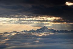 Glowing sun rays illuminate snowy Julian Alps and sea of clouds. Jagged snowy range of Julian Alps with Triglav peak the highest Slovenian mountain towers above Stock Photo