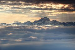 Jagged snowy Triglav peak rises dramatically over sea of clouds. Jagged snowy peaks of Julian Alps range and Triglav, highest mountain of Slovenia, towering Stock Photo