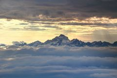 Jagged snowy Triglav peak rises over sea of clouds at sunset royalty free stock photos