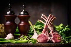 Jagnięcy naczynia kucharstwo z świeżym barankiem dręczy od masarki na ciemnym nieociosanym kuchennym stole przy drewnianym tłem Zdjęcia Royalty Free