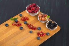 Jagod malinki, agresty i czernicy w szklanych pucharów stojaku na tnącej desce z jagodami czerwoni rodzynki, i Fotografia Royalty Free