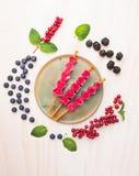 Jagoda lody strzela z czerwonym rodzynkiem, czernicami, czarnymi jagodami i miętowymi liśćmi komponuje na białym drewnianym tle, Obraz Royalty Free