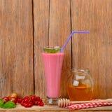Jagodowy smoothie i miód na drewnianym sura Zdjęcie Royalty Free