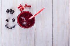Jagodowy smoothie na białym drewnianym tle Świeże jagody, czarne jagody, czernicy gofr z smiley twarzą Odgórny widok, mieszkanie fotografia stock
