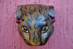 Jaguar head carved in wood decoration. On a pink wall Royalty Free Stock Image