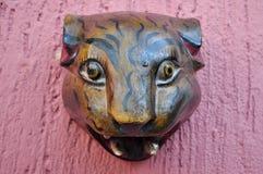 Jaguar-Kopf schnitzte in der hölzernen Dekoration auf einer rosa Wand Stockbild