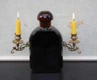 Jaguar per gli uomini, Eau de Toilette, grande bottiglia di profumo davanti ai candelabri di un piano con le candele brillanti fotografia stock