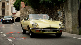 Jaguars at Bergamo Historic Grand Prix 2015. A yellow Jaguar E-Type followed by a black F-Type driving down Boccola street in Citta' Alta (the medieval part of Stock Photo