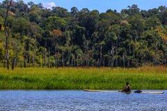 Jahai aboriginer som paddlar en flotte i kungliga Belum Royaltyfria Bilder