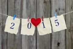 Jahr 2015 auf antikem Papier mit dem roten Herzen, das an der Wäscheleine durch schäbigen hölzernen Zaun hängt Stockbild