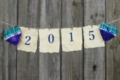 Jahr 2015 auf antikem Papier mit den blauen und grünen Herzen, die an der Wäscheleine durch hölzernen Zaun hängen Lizenzfreie Stockfotos