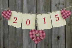 Jahr 2015 auf antikem Papier mit den roten Herzen, die an der Wäscheleine durch hölzernen Zaun hängen Lizenzfreie Stockbilder