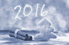 Jahr 2016 geschrieben auf Grau, heller Hintergrund Schneeflakfeuerbild Zuckerstange im Schnee Weihnachtsbaum Keks und cinnamons s Lizenzfreies Stockfoto