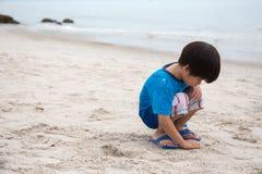 4 Jahre alte asiatische Jungensandschreiben einsam auf Strand mit Seebac Lizenzfreie Stockfotografie