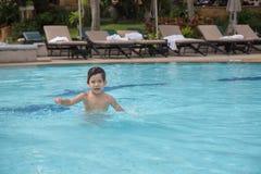 4 Jahre alte asiatische Kinderschwimmen einsam im sauberen Swimmingpool Lizenzfreies Stockfoto