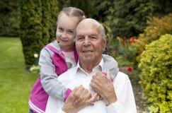 95 Jahre alte englische Mann mit Enkelin im Garten Lizenzfreies Stockfoto