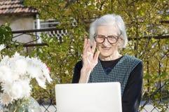 90 Jahre alte Frau, die beim Haben eines Videoanrufs wellenartig bewegen Lizenzfreie Stockfotografie