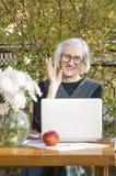 90 Jahre alte Frau, die beim Haben eines Videoanrufs wellenartig bewegen Stockfotografie