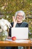 90 Jahre alte Frau, die beim Haben eines Videoanrufs wellenartig bewegen Stockfoto