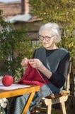 90 Jahre alte Frau, die eine rote Strickjacke stricken Lizenzfreie Stockfotos