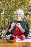 90 Jahre alte Frau, die eine rote Strickjacke stricken Stockbilder