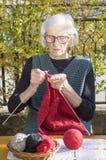 90 Jahre alte Frau, die eine rote Strickjacke stricken Stockfoto